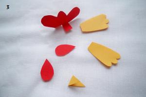 Wycięte z papieru elementy do kogucika, czerwony grzebień i dzwonki, żółty dziób i skrzydła