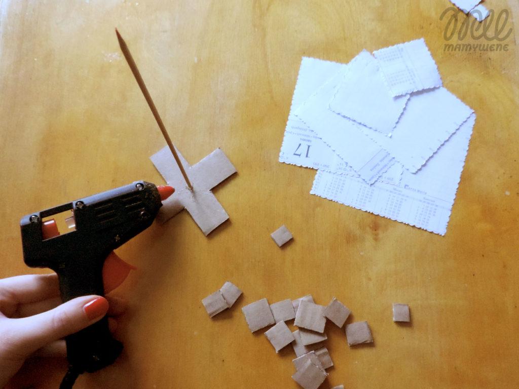 Tekturowa podstawa w kształcie krzyżyka przyklejana do końca wykałaczki klejem na gorąco. Obok leżą małe kawałki tektury i wycięte papierowe kwadraty ze wzorem.
