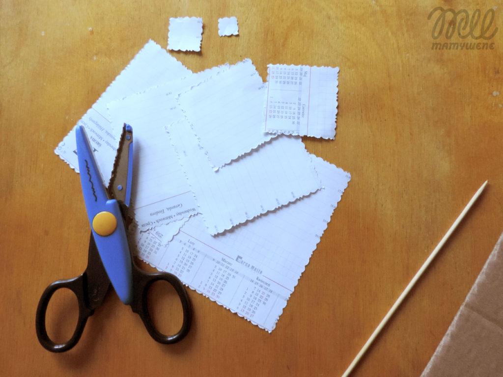 Różnej wielkości papierowe kwadraty wycięte nożyczkami ze wzorem, na nich nożyczki. Obok wykałaczka i tektura.