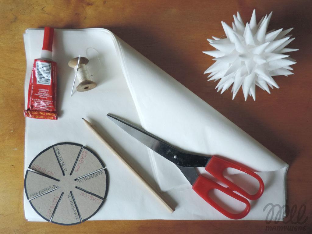 Materiały potrzebne do wykonania ozdoby: papier śniadaniowy, szablon, ołówek, nożyczki, klej, nitka z igłą. Obok leży przykład gotowego jeża.